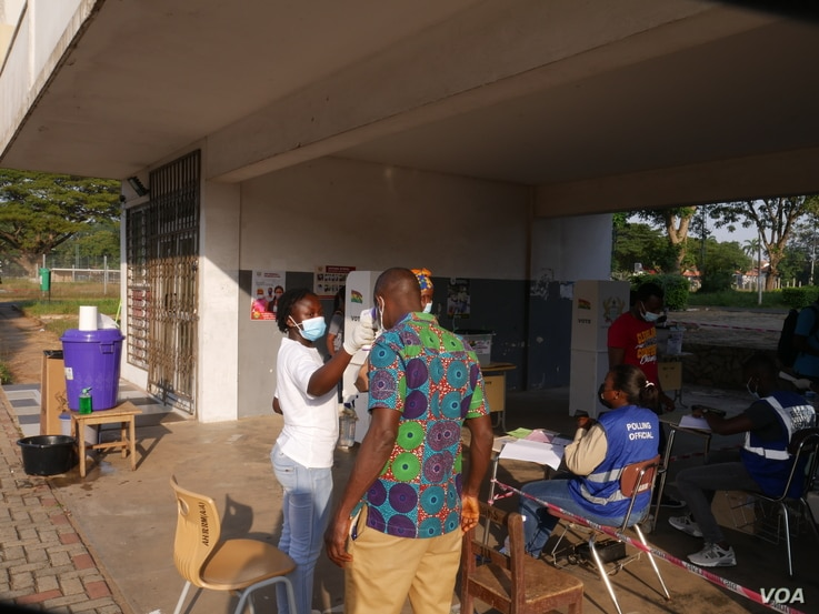 Voters have their temperature checked before casting their ballots, in Accra, Dec 7, 2020 (Stacey Knott/VOA)