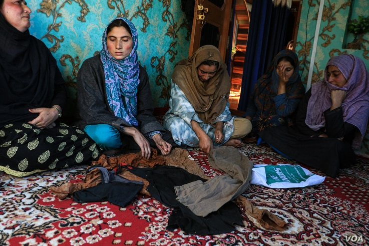 Family members of an Indian soldier, Shakir Manzoor, displaying his clothes after they were found in an orchid by his father in Shopian district of Indian administered Kashmir. (UbaidUllah Wani/VOA)