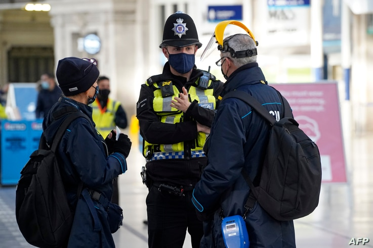 A member of the British Trasport Police speaks with travelers at Waterloo Station in London, Dec. 20, 2020.