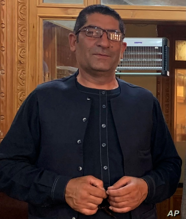 FILE  - Afghan journalist Rahmatullah Nikzad poses for photograph in Kabul, July 29, 2019.