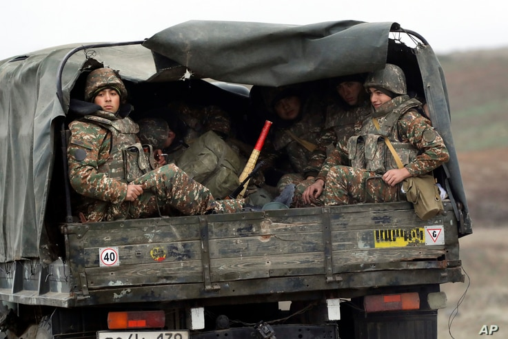 Ethnic Armenian soldiers sit in a military truck on a road during the withdrawal of troops from the separatist region of Nagorno-Karabakh, Nov. 19, 2020.