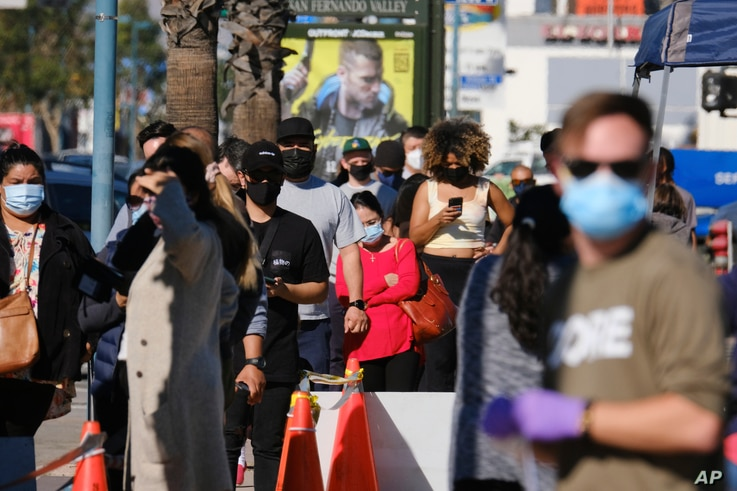 People wait in line to be tested at an outdoor COVID-19 testing site in the North Hollywood section of Los Angeles, California, Dec. 5, 2020.