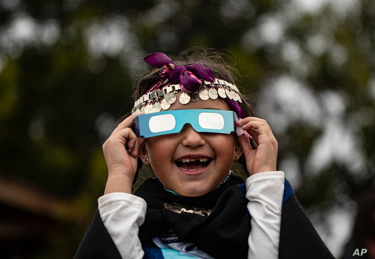 Magdalena Nahuelpan, a Mapuche Indigenous girl, looks at a total solar eclipse using special glasses in Carahue, La Araucania, Chile.