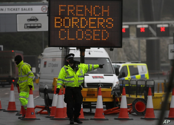A police officer directs traffic at the entrance to the closed ferry terminal in Dover, England, after the Port of Dover was closed and access to the Eurotunnel terminal suspended following the French government's announcement.
