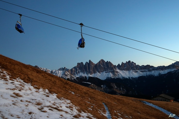 A chairlift is pictured in front of the Geisler group massif at the Dolomites mountains near Bressanone, autonomous region of South Tyrol, northern Italy's German-Italian speaking region, Nov. 26, 2020.