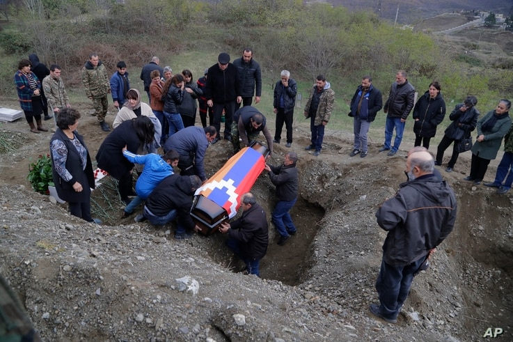 FILE - Relatives and friends of Mkhitar Beglarian, an ethnic Armenian soldier of the Nagorno-Karabakh army, killed during fighting in the enclave, lower his coffin into a grave during his funeral in Stepanakert, Nov. 15, 2020.