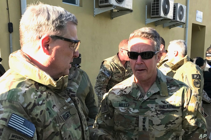 Chairman of the U.S. Joint Chiefs of Staff Gen. Mark Milley, left, talks with Gen. Scott Miller, the commander of U.S. and coalition forces in Afghanistan, Dec. 16, 2020, in Kabul, Afghanistan, before holding a meeting with Taliban peace negotiators.