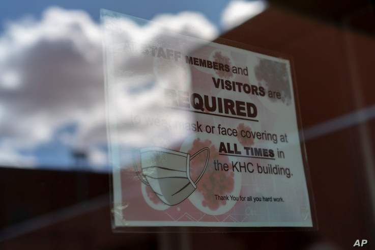 FILE - A sign on a door warns people to wear face coverings, at the Kayenta Health Center on the Navajo reservation in Kayenta, Arizona, April 18, 2020. Across the nation, Native American tribes are working to protect their oldest members from COVID.