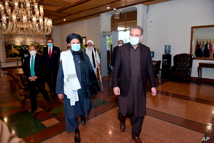 Pakistan's Foreign Minister Shah Mahmood Qureshi, right, and Mullah Abdul Ghani Baradar, head of a Taliban political team, arrive at the Foreign Ministry for talks, in Islamabad, Dec. 16, 2020. (Photo provided by Pakistan's Ministry of Foreign Affairs)