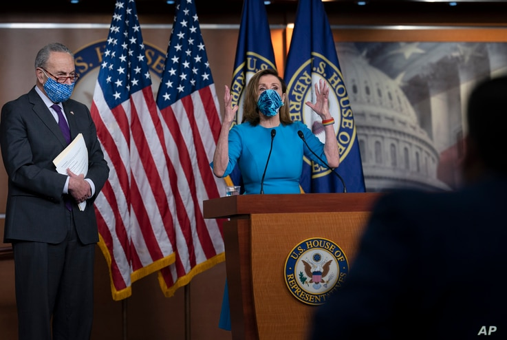 FILE - House Speaker Nancy Pelosi and Senate Minority Leader Chuck Schumer, left, meet with reporters on Capitol Hill in Washington, Nov. 12, 2020.
