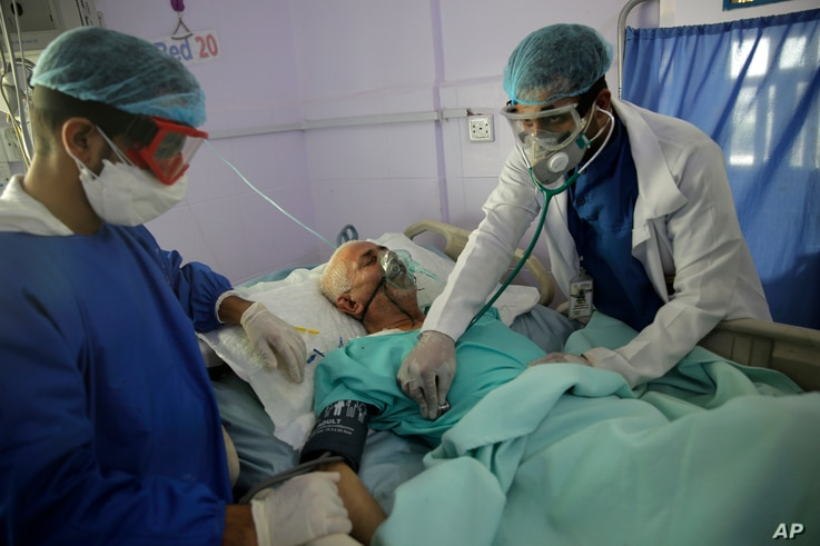 FILE - Medical workers attend to a COVID-19 patient in an intensive care unit at a hospital in Sana'a, Yemen, June 14, 2020.