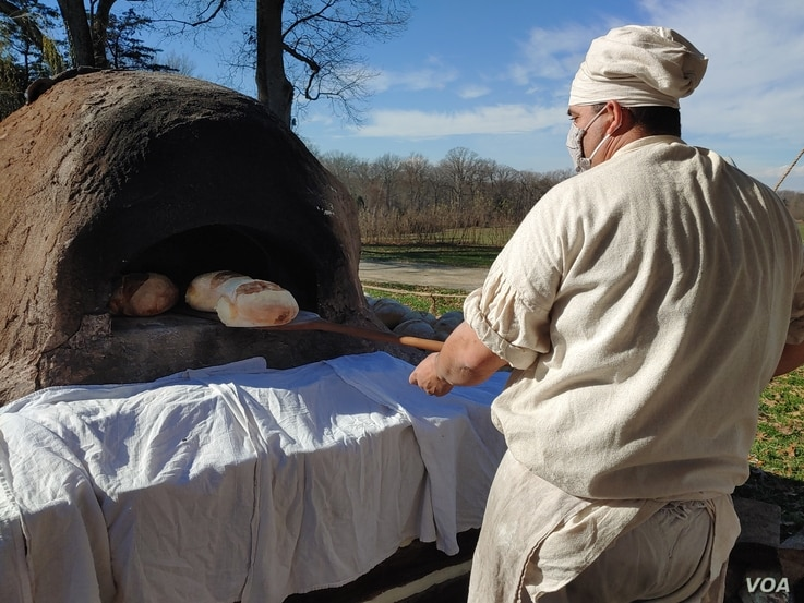 Justin Cherry bakes bread in a clay, wood-fired oven he made. He uses the same kind of wheat that was grown on Mount Vernon