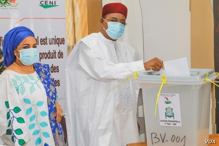 Incumbent President Mahamadou Issoufou, pictured with his wife, Aissata Issoufou Mahamadou, casts his vote in Niamey, Dec. 27, 2020. (Mahmud Lalo/VOA Hausa)