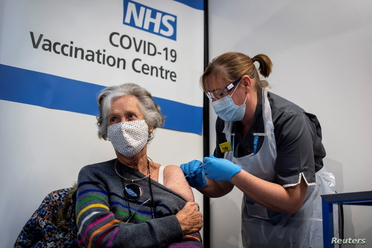 A woman receives the first of two Pfizer-BioNTech COVID-19 vaccine jabs, at Guy's Hospital, in London, Britain, Dec. 8, 2020.