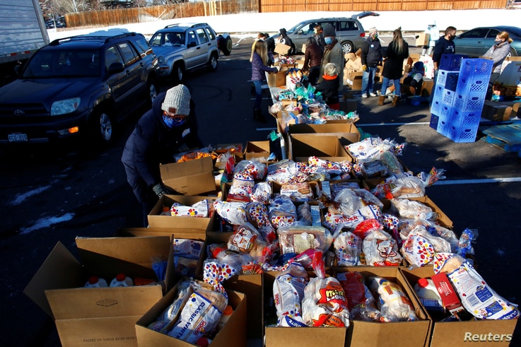 People line up in their cars in the parking lot of St. James Presbyterian Church in Littleton, Colorado, to receive food donations from Food Bank of the Rockies ahead of Thanksgiving, Nov. 25, 2020.