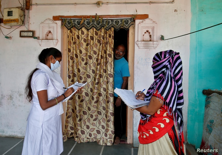 Health workers collect personal data during a door-to-door survey for the first shot of COVID-19 vaccine for people above 50 years of age and those with comorbidities, in a village on the outskirts of Ahmedabad, India, Dec. 14, 2020.