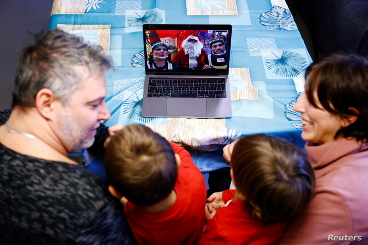 Gabriele Vinzi, 3, and his brother Samuele Vinzi, 4, react along with their parents as they receive a call via Zoom by a man dressed as Santa Claus, amid theCOVID-19 pandemic, in Rome, Italy, Dec. 8, 2020.