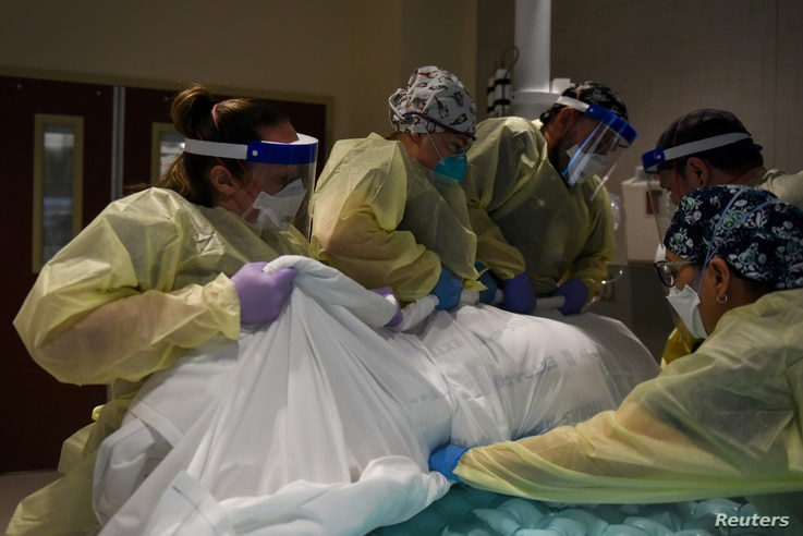 Healthcare personnel rotate a patient who is on a ventilator at a hospital in Hutchinson, Kansas, Nov. 20, 2020.