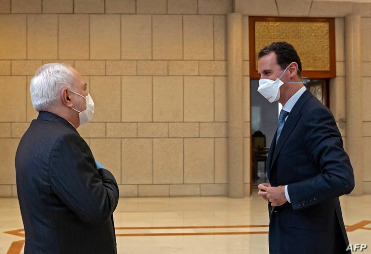 A handout picture released by the official Syrian Arab News Agency (SANA) on April 20, 2020, shows President Bashar Al-Assad (R…