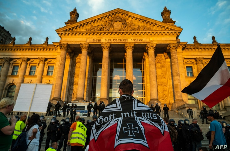 A demonstrator wrapped in a flag of the German empire faces off with riot policemen standing guard in front of the Reichstag…