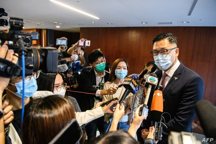Pro-democracy lawmaker Lam Cheuk-ting (R) speaks to reporters after displaying two banners outside the main chamber of the…