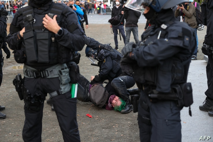 """A protester from the initiative """"Querdenken"""" which opposes coronavirus restrictions is detained by police during a…"""