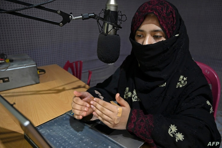 In this photo taken on September 29, 2020, radio presenter Shukria Wali, 18, reads the news during a broadcast at the Merman…