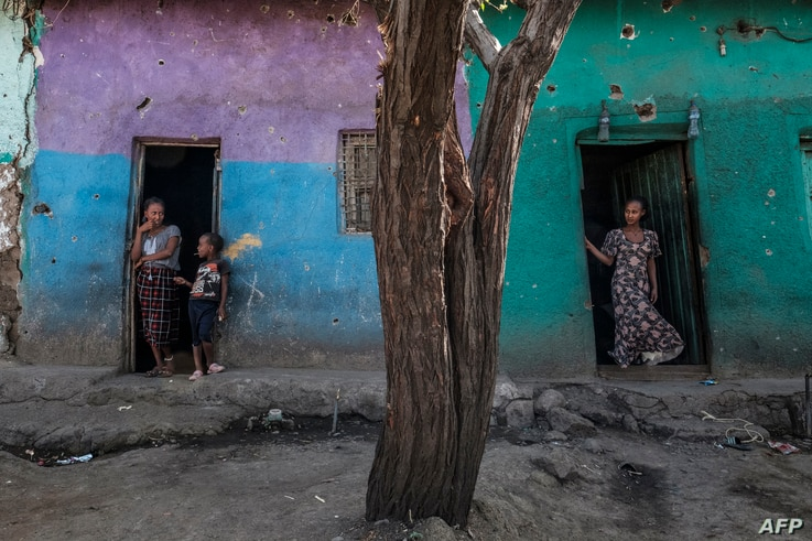 People stand at the doors of house that were damaged by shelling in the town of Mehoni, Ethiopia, on December 11, 2020. The…