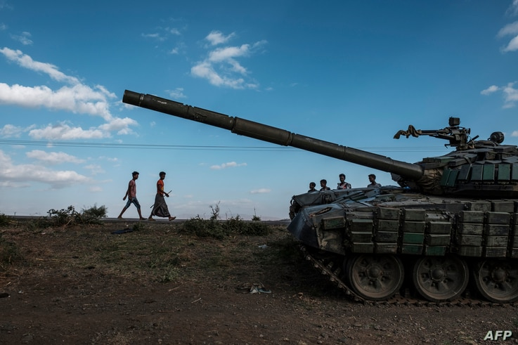 Youngsters walk next to an abandoned tank belonging to Tigrayan forces south of the town of Mehoni, Ethiopia, on December 11,…