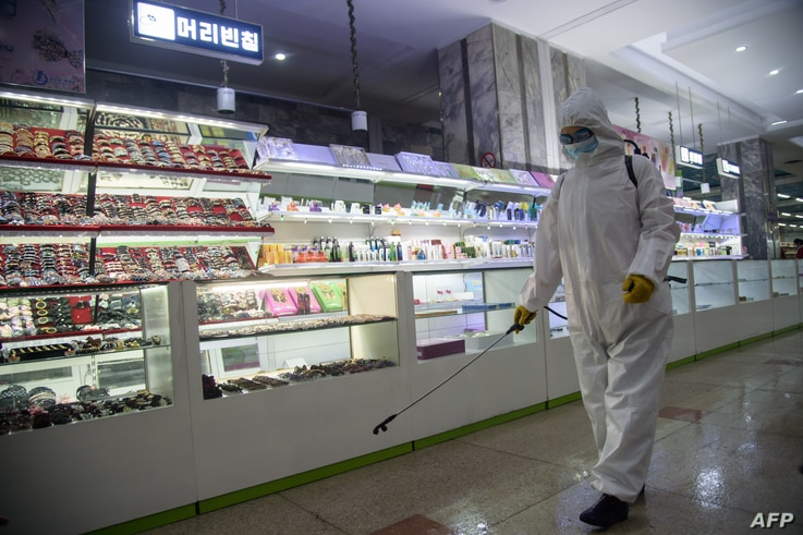 A health worker sprays disinfectant inside the Pyongyang Department Store No. 1 prior to opening for business, in Pyongyang on...