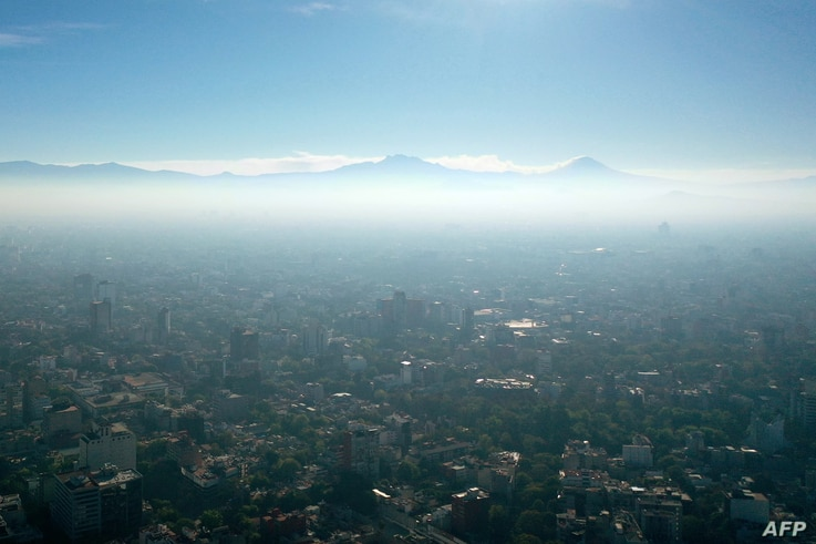 Aerial view showing low visibility due to air pollution in Mexico City, on January 1, 2021, during the COVID-19 coronavirus…