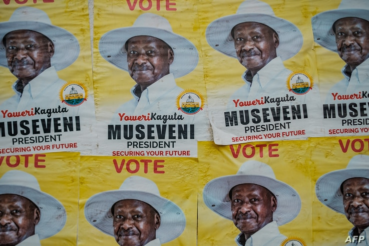 Posters of Uganda's President Yoweri Museveni who is running for his 6th presidential term are seen on a wall in Kampala,…