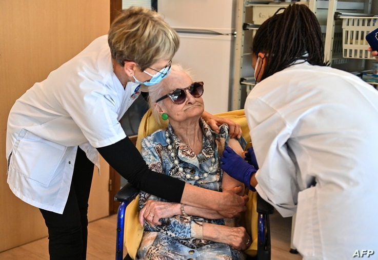 A doctor administers a dose of Pfizer-BioNtech coronavirus disease (Covid-19) vaccine to an old woman on January 4, 2020