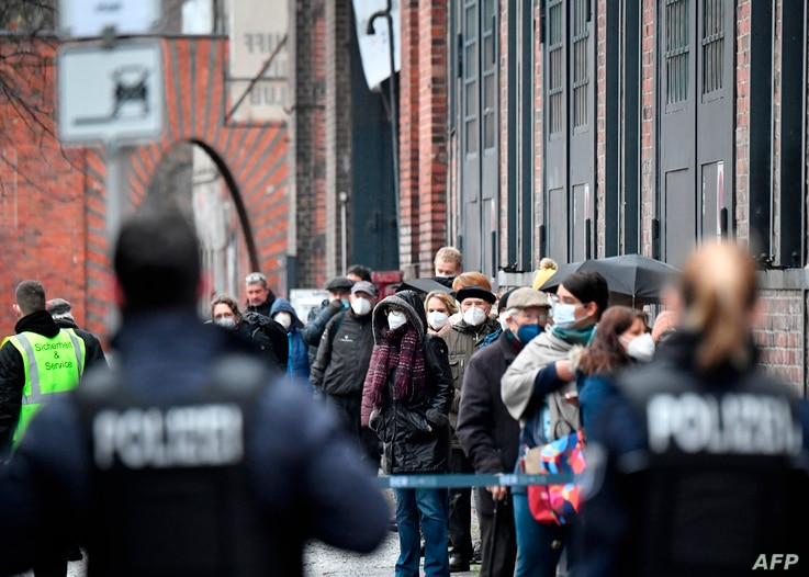 Police stand by as people wearing face masks queue to get access to the vaccination center at the 'Arena' in Berlin's Treptow…