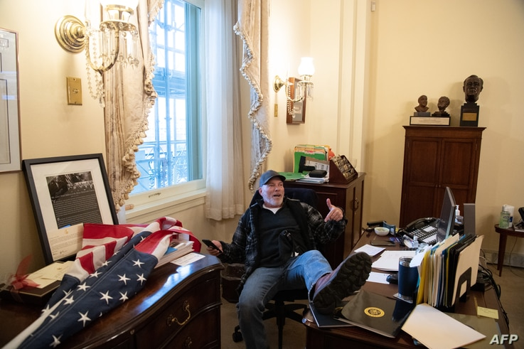 Richard Barnett, a supporter of US President Donald Trump sits inside the office of US Speaker of the House Nancy Pelosi as he...