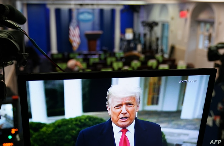 US President Donald Trump is seen on TV from a video message released on Twitter addressing rioter at the US Capitol, in the…