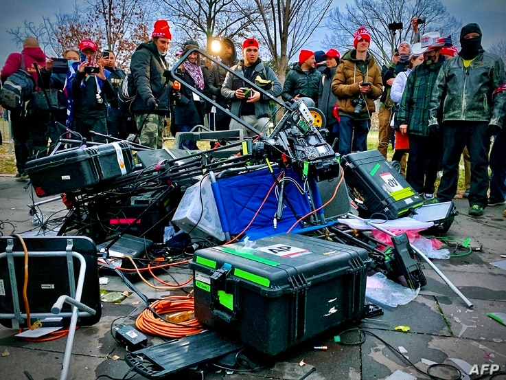 Supporters of US President Donald Trump stand next to media equipment they destroyed during a protest on January 6, 2021…
