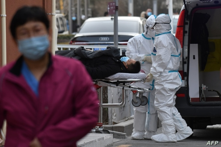 Medical workers wearing protective suits as a precaution against the COVID-19 coronavirus deliver a patient to the fever clinic…