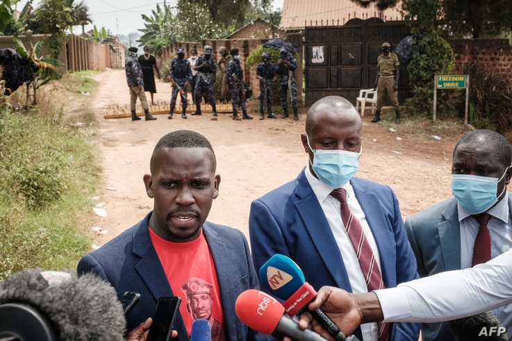 Joel Ssenyohy (L), spokesperson of National Unity Platform (NUP), speaks to media with Benjamin Katana (C) and George Musisi,…