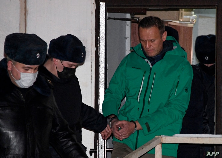 Opposition leader Alexei Navalny is escorted out of a police station on January 18, 2021, in Khimki, outside Moscow, following…