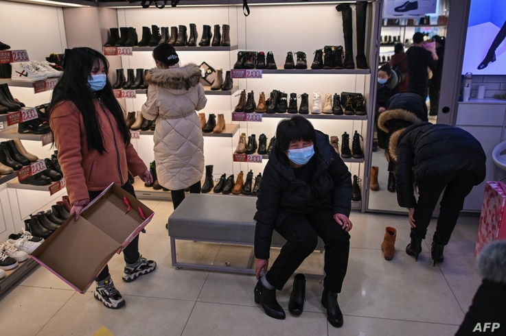 People wearing face masks as a preventive measure against the Covid-19 coronavirus visit a shoe shop in Wuhan, China's central…