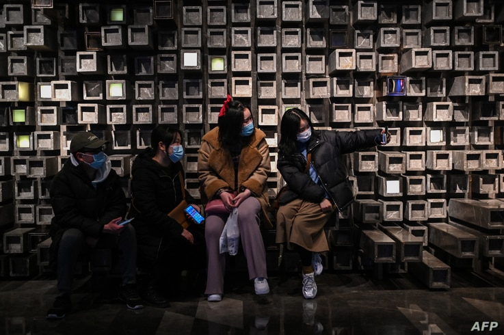 In this picture taken on January 22, 2021, people take a selfie in a shopping mall in Wuhan, China's central Hubei province. …