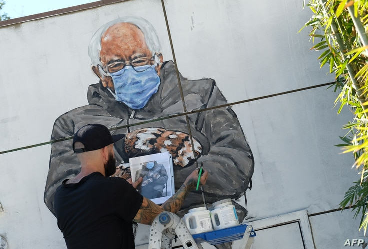 Artist Jonas Never (@never1959) paints a mural of Senator Bernie Sanders in Culver City, California on January 24, 2021. Standing out in a crowd of glamorously dressed guests, Bernie Sanders showed up for the US presidential inauguration in a heavy winter jacket and patterned mittens -- with an AFP photo of the veteran leftist spawning the first viral meme of the Biden era.