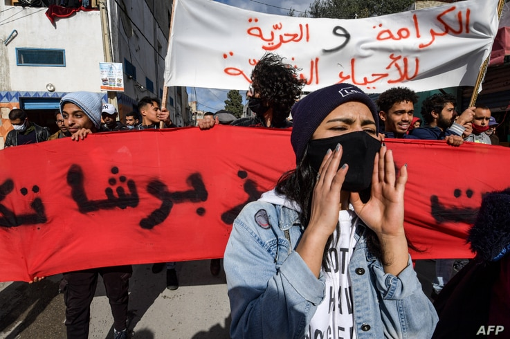 Protesters from the Ettadhamen city suburb on the northwestwern outskirts of Tunisia's capital Tunis march on January 26, 2021…
