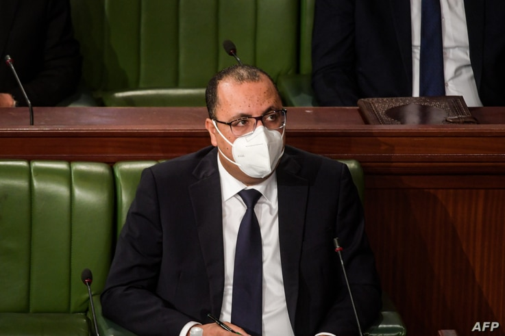 Tunisian Prime Minister Hichem Michichi, mask-clad due to the COVID-19 coronavirus pandemic, attends the presentation of his…