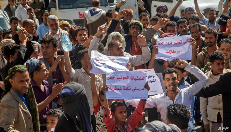 Opposers of Yemen's Huthi rebels hold placards during a rally in support of the United States and the outgoing Trump…