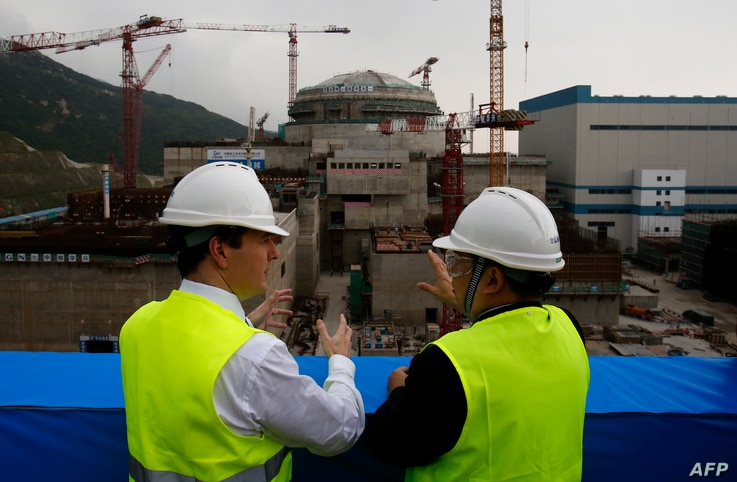British Chancellor of the Exchequer George Osborne (L) talks with Taishan Nuclear Power Joint Venture general manager Guo...