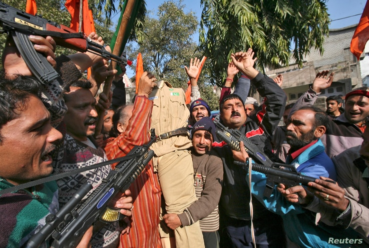 FILE - Supporters of Shiv Sena, a Hindu hardline group, shout slogans as they hold toy guns and an effigy depicting a Pakistani soldier during a protest in Jammu January 11, 2013.