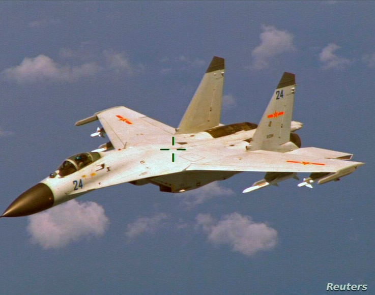 A Chinese J-11 fighter jet is seen flying near a U.S. Navy P-8 Poseidon about 215 km (135 miles) east of China's Hainan Island…