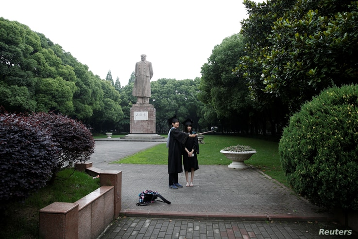 Students take pictures in front of the statue of Chinese leader Mao Zedong after their graduation ceremony at Fudan University…